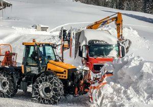 Schneeräumung mit JCB Fastrac, Holzlastwagen MAN, Kettenbagger